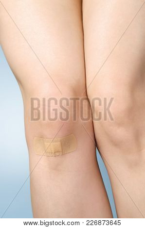 Female Leg With Adhesive Bandage On Blue Background