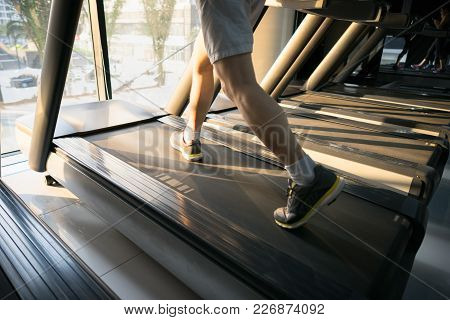 Machine Treadmill With People Running Closeup At Fitness Gym