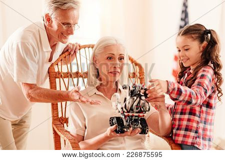 What Is This. Excited Girl And Her Grandfather Joining Their Grandmother Relaxing In A Rocking Chair