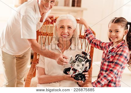 Harmonious Relations. Adorable Family Members Looking Into The Camera With Cheerful Smiles On Their