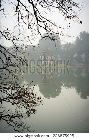 Turtle Tower (thap Rua) With Dry Branches Of Tree On Foreground In Misty Morning. Winter Season At H
