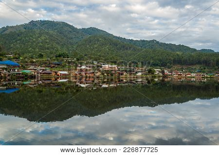 Water Village At The Edge Of River In Front Of The Mountain In Countryside Of Thailand