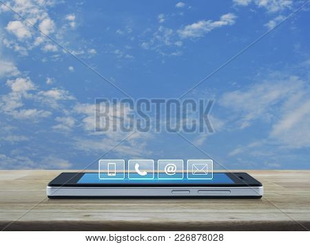Telephone, Mobile Phone, At And Email Buttons On Modern Smart Phone Screen On Wooden Table Over Blue