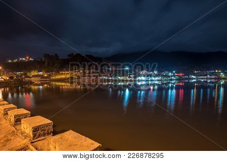 Water Village At The Edge Of River In Front Of Mountain In Night Of Countryside, Thailand