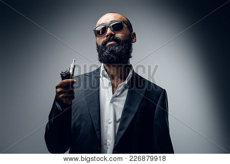 Hairless Bearded Male In Sunglasses, Dressed In A Suit Holds Electronic Cigarette.