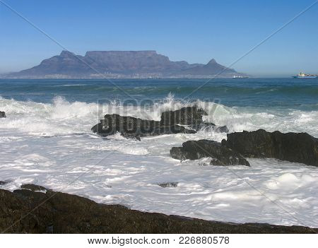 Waves Washing Over Some Boulders In The Fore Ground And Table Mountain In The Back Ground