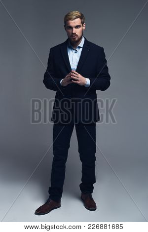 Confident And Thinking. A Full-length Portrait Of Businessman Holding Hands Together Standing In Fro