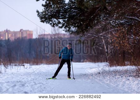 Photo Of Male Skier In Blue Jacket In Winter Park On Background Of Houses