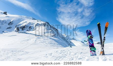 Photo Of Crossed Skis And Sticks Against Background Of Snowy Landscape During Day