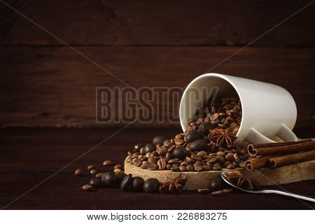 Coffee Grain Is Poured From The White Cup, Cinnamon, Chocolate Balls On A Dark Wooden Background. Co