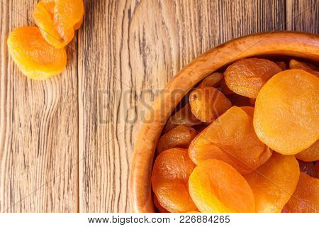 Dried Apricots, Dried Fruits In A Wooden Plate. Rustic Style. Healthy Diet. Place For Text.