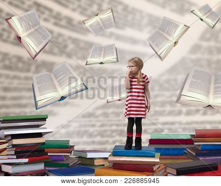 A Small Child With Glasses Standing Among The Books. The Concept Of Education And Reading. Preparati