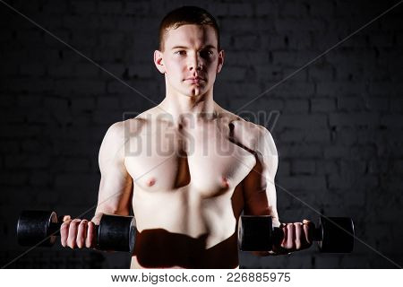 Close-up Of Handsome Power Athletic Man Training Pumping Up Muscles With Dumbbells