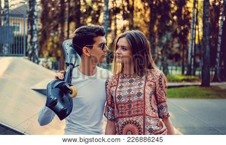Guy With Skateboard And Attractive Young Female In A Park.