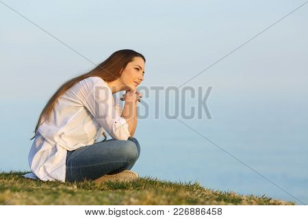 Relaxed Woman Thinking And Looking Away Sitting On The Grass On The Beach