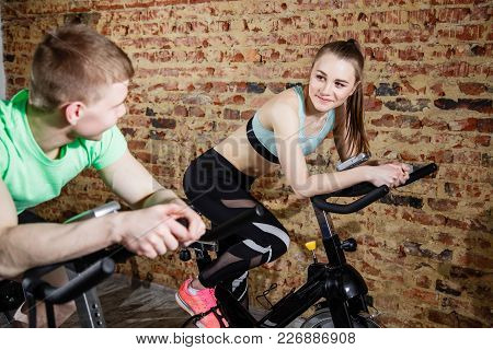 Young Woman And Man Wearing Training On Cycling Machines In Light Spacious Gym.
