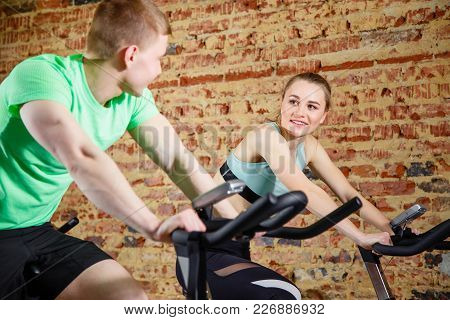 Young Man Talking To A Cute Blonde While They Both Do Some Cardio On A Bicycle At The Gym. Focus On