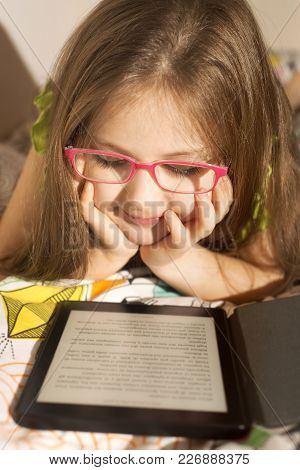Little Caucasian 6-8 Years Old Girl Reading A E-book Reader In The Bed Before Sleep. Children And Te