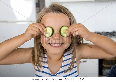 Young Beautiful And Adorable Girl 6 Or 7 Years Old Having Fun At Home Kitchen Putting Cucumber Slice