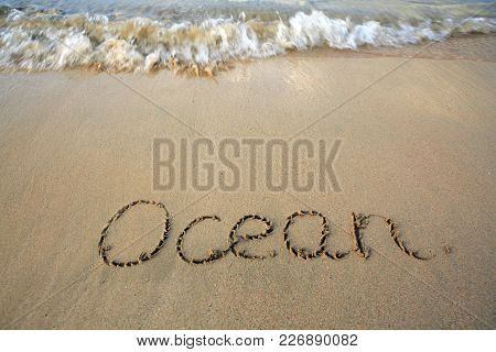 Word Ocean Written On The Sand Near The Sea. Travel Background.