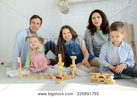Day Off In A Big Family. Dad, Mom And Three Children Are Sitting On The Floor. Younger Children Are