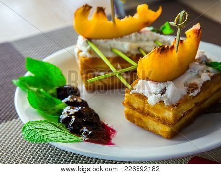 Delicious Dessert For Holidays Cake On A Plate With Peaches, Jam And Fresh Mint Leaves