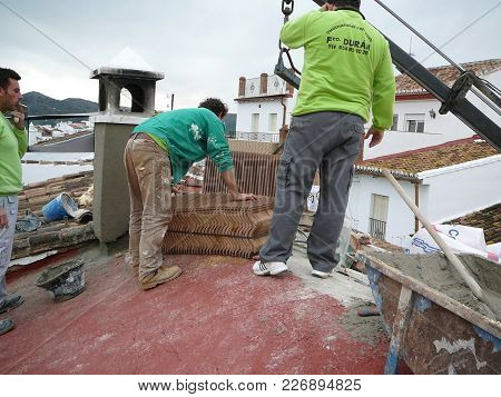 Alora, Spain - November 24, 2011: Men Receiving Roof Tiles On Roof Of Village House In Andalusia