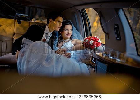 Wedding Portrait. Happy Young Stylishly Dressed Couple Is Sitting In The Car And Looking Through Win
