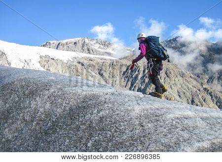 A Climber Makers Her Way Up The Fox Glacier With Typical Mountaineering Safety Gear. South Island Of