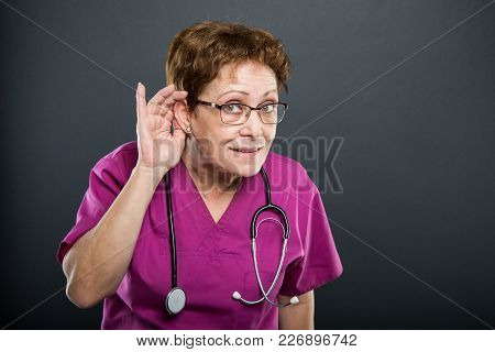 Portrait Of Senior Lady Doctor Showing Can't Hear Gesture