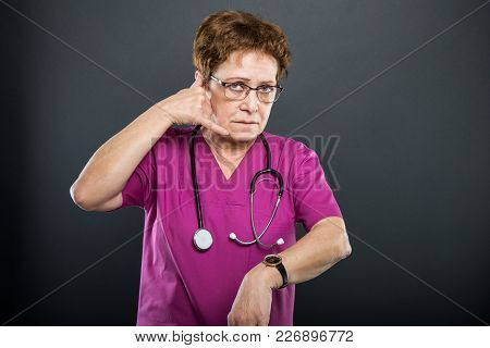 Portrait Of Senior Lady Doctor Showing Calling Late Gesture