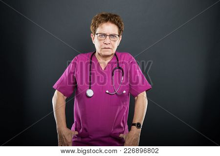 Portrait Of Senior Lady Doctor Angry With Hands In Pockets