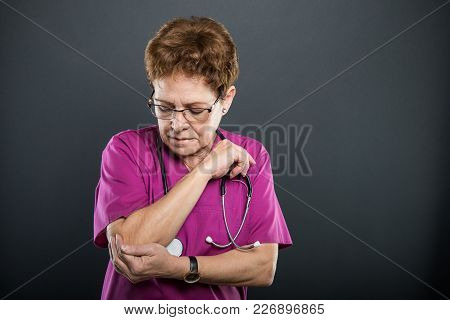 Portrait Of Senior Lady Doctor Holding Elbow Like Hurting