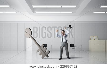 Determined Businessman In Modern Interior Breaking With Hammer Stone Key Figure