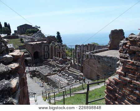 Taormina, Sicily Italy On May 2016: Ruins Of Ancient Greek And Roman Theatre In Italian City, Seasid