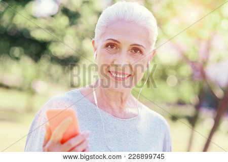 Modern Life. Close Up Of Optimistic Elderly Woman Using Mobile Phone While Listening To Music And Ex