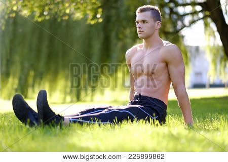 Shirtless Abdominal Young Male Fitness Model Sits On A Grass In A Park.