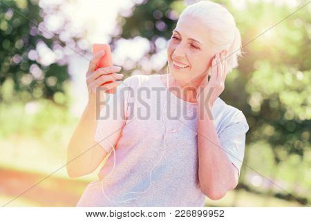 Sweet Song. Close Up Of Positive Elderly Woman Using Mobile Phone While Listening To Music And Expre