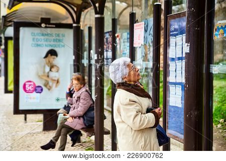 Lisbon, Portugal - January, 2018. An Elderly Gray-haired Beautiful Retired Woman At A Bus Stop Looks