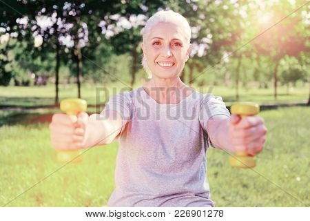 Getting Fit. Portrait Of Cheerful Elderly Woman Keeping Weights In Hands In Front Of You While Expre