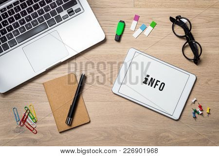 Info Writing On Tablet Screen With Laptop, Notebook And Glasses Lying On Wooden Office Desk As Flat