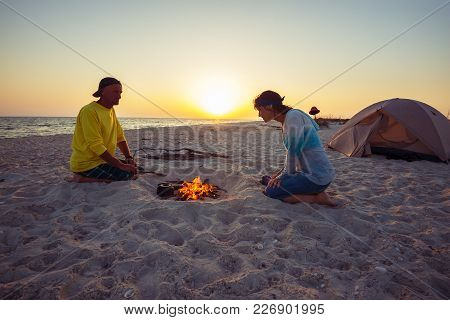 Couple Of Happy Adventurers Sit Next To Burning Bonfire On The Beach, Admire Flame And Going To Drin