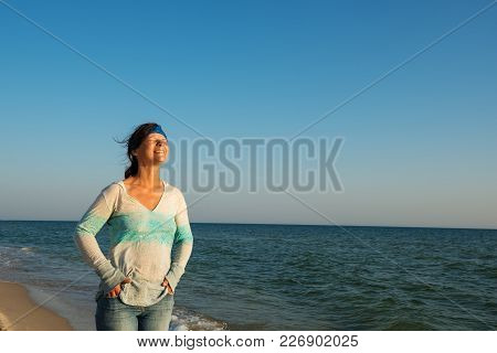 Woman Traveler Laughs, Squeezed Her Eyes From Happiness, Stands On The Sea Coast, Has Fun And Enjoys