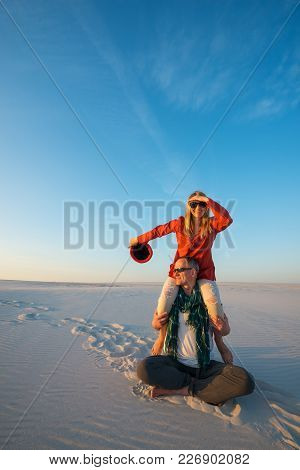 Smiling Couple, Man With A Laughing Girl On His Shoulders, Sits In Desert On A Sunny Evening, Fools