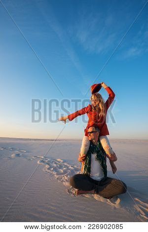Joyful Crazy Couple, Man With A Expressive Girl On His Shoulders, Sits In Desert On A Sunny Evening,