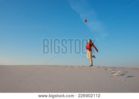 Happy Young Woman, Blonde Dances In The Desert, Admires The Flight Of Her Hat In The Blue Sky And Ha