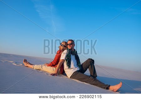 Happy Couple Sitting, Back To Back, In The Desert Against A Blue Sky On A Sunny Evening, Smiling And
