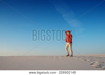 Modern Young Woman, Blonde Walks In The Desert, Admires Magic Landscape And Dreams On Sunny Evening.