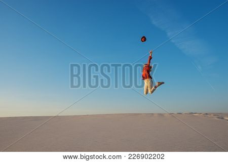 Expressive Young Woman, Blonde Energetically Jumps On The Desert On The Background Of The Blue Sky,