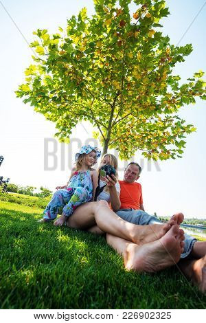 Joyful Parents With Small Laughing Daughter Taking Selfie In The Park Against The Background Of A Gr